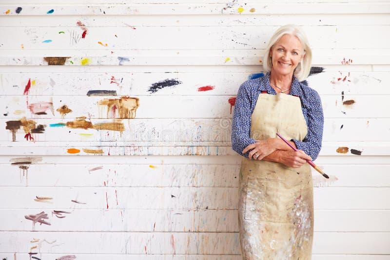 Stående av den kvinnliga konstnärAgainst Paint Covered väggen arkivbild
