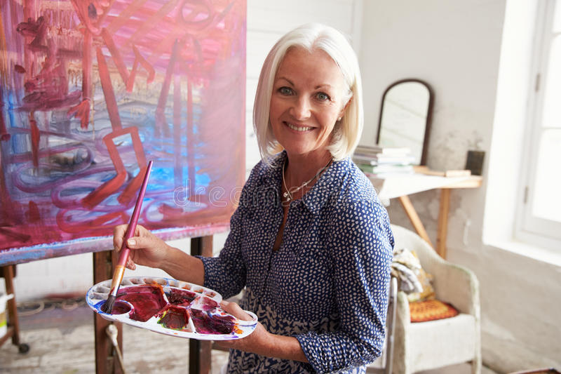 Stående av den kvinnliga konstnären Working On Painting i studio royaltyfria foton