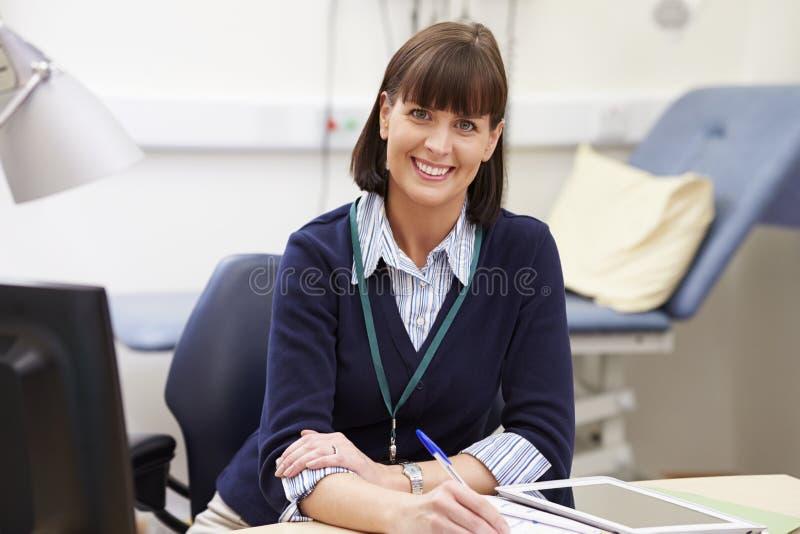 Stående av den kvinnliga konsulenten Working At Desk i regeringsställning arkivbild