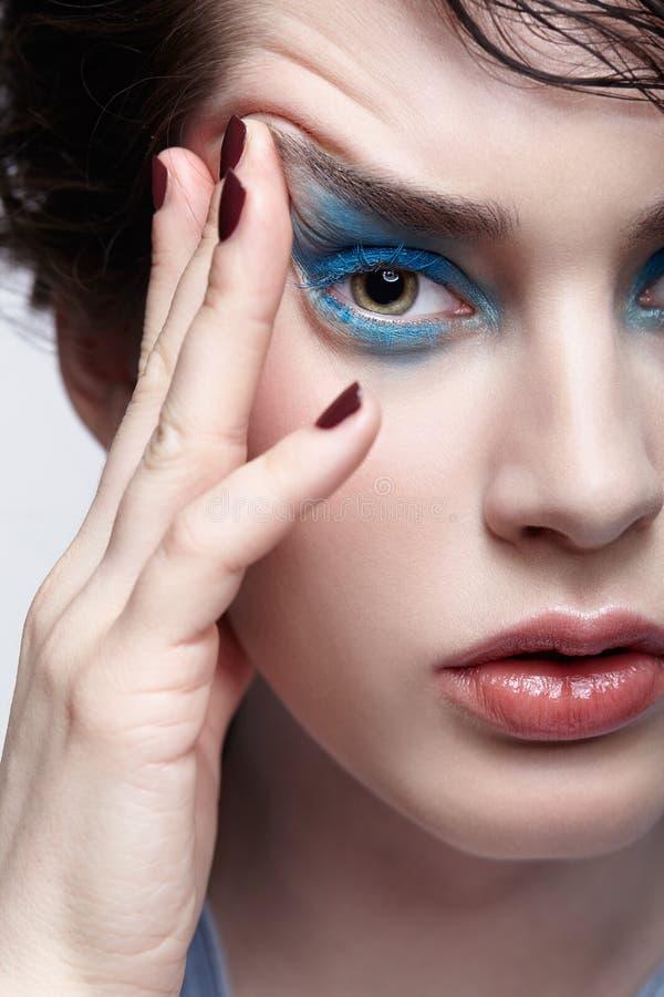 Stående av den kvinnliga kvinnan med ovanlig skönhetmakeup och vått hår och blått skuggasmink arkivbild