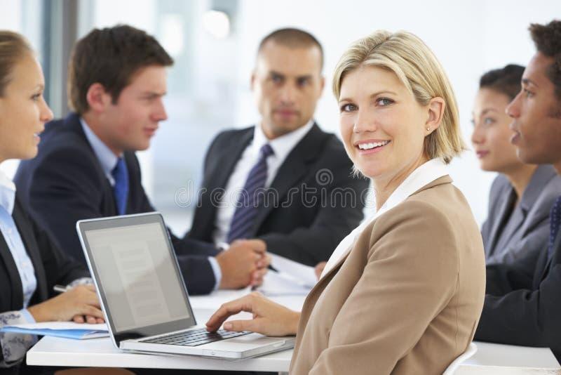 Stående av den kvinnliga ledaren med kontorsmöte i bakgrund arkivfoto