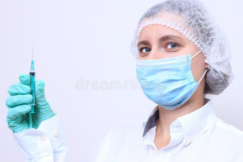 Stående av den kvinnliga medicinska professionelln i maskering med injektionssprutan royaltyfri fotografi