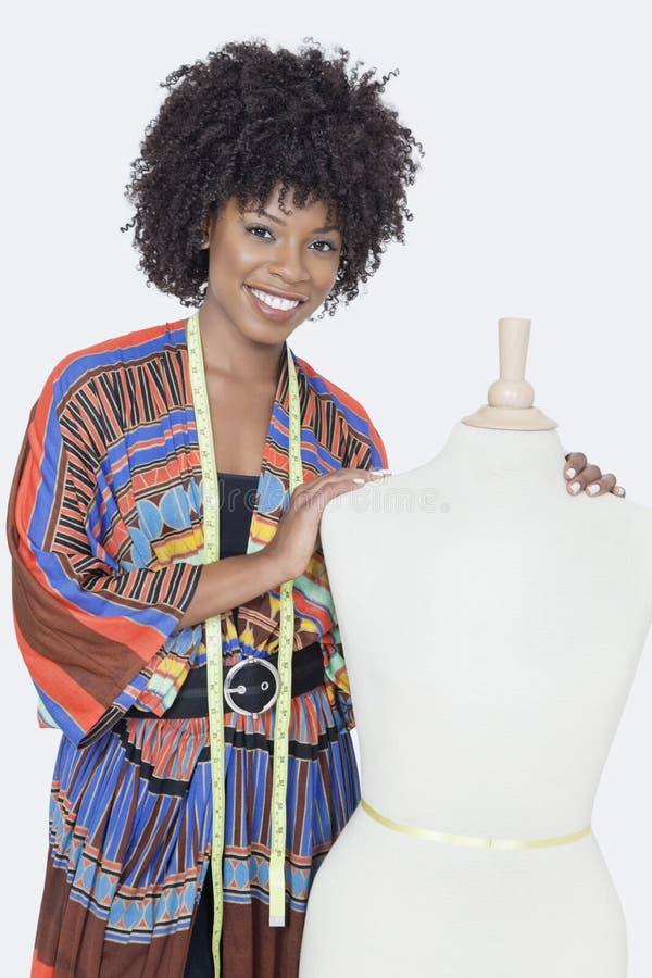Stående av den kvinnliga modeformgivaren för afrikansk amerikan med skräddares attrapp över grå bakgrund royaltyfri foto
