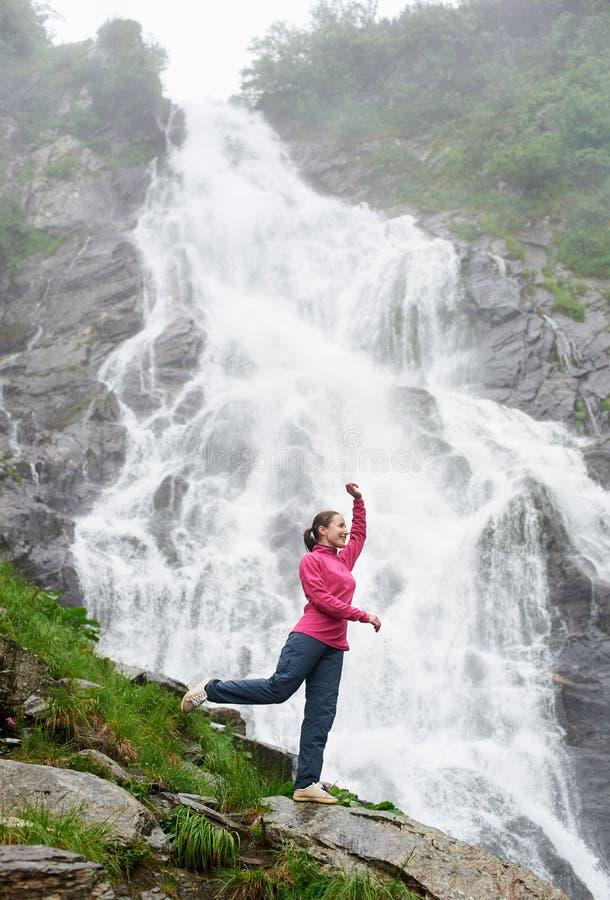 Stående av den kvinnliga modellen mot vattenfallet Balea i Fagarash berg royaltyfri foto