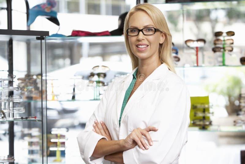 Stående av den kvinnliga optiker By Glasses Display royaltyfri foto