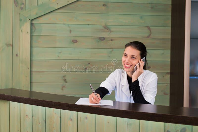 Stående av den kvinnliga receptionisten som förklarar formen till patienten i tandläkareklinik royaltyfria bilder