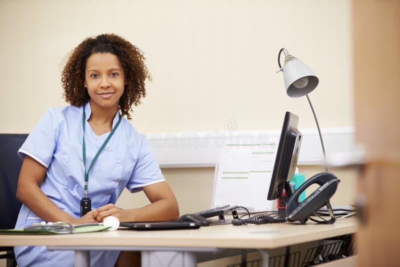 Stående av den kvinnliga sjuksköterskan Working At Desk i regeringsställning arkivfoto