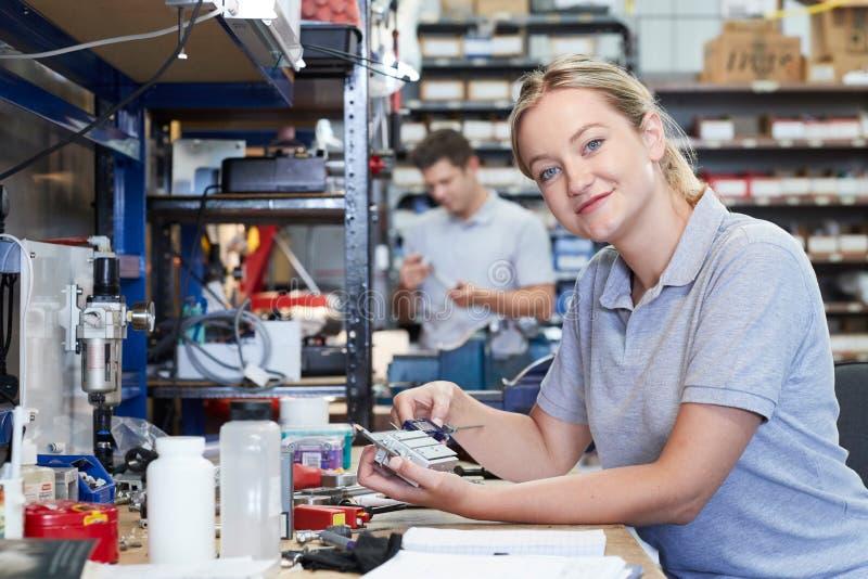 Stående av den kvinnliga teknikerIn Factory Measuring delen på Wo fotografering för bildbyråer