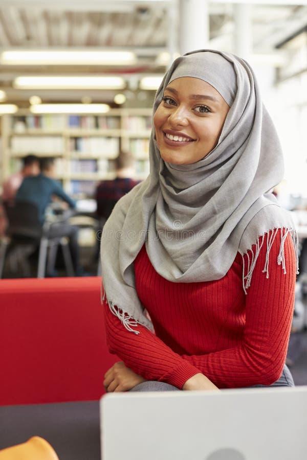 Stående av den kvinnliga universitetsstudenten Working In Library arkivfoton