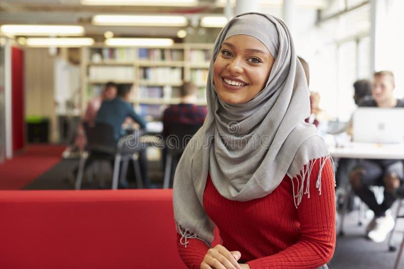 Stående av den kvinnliga universitetsstudenten Working In Library fotografering för bildbyråer