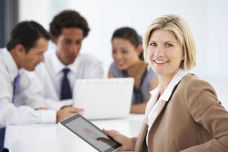 Stående av den kvinnliga utövande användande minnestavladatoren med kontorsmöte i bakgrund fotografering för bildbyråer