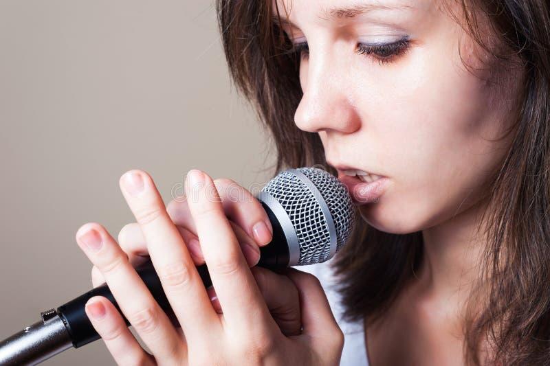 Stående av den kvinnliga vokalisten på den gråa bakgrundscloseupen arkivbild