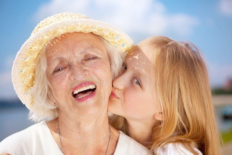 Stående av den kyssande farmodern och sondottern som ser arkivfoton