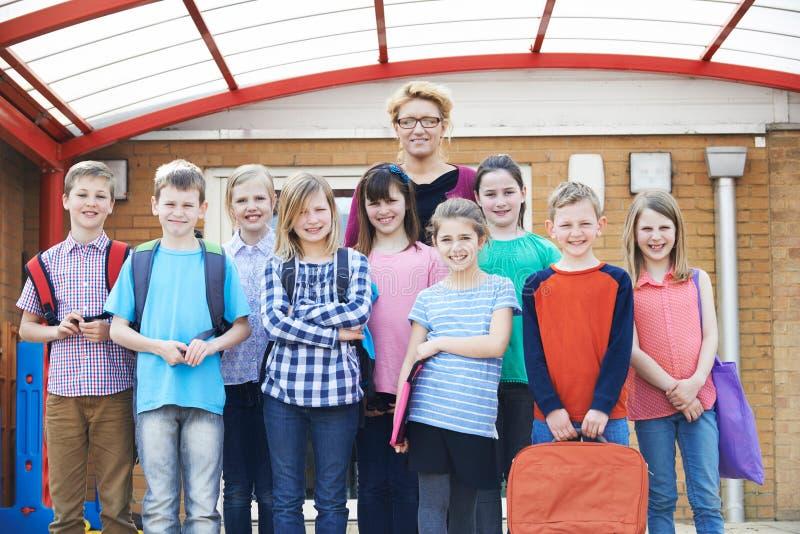 Stående av den lärareWith Pupils In lekplatsen arkivfoto