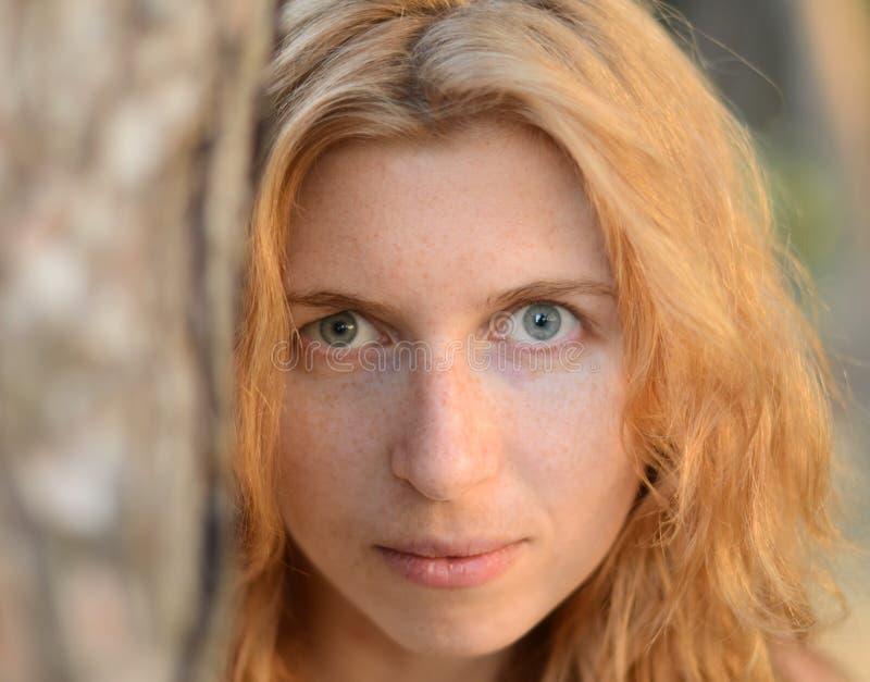 Stående av den lösa och mystiska rödhåriga flickan i skogen royaltyfri foto