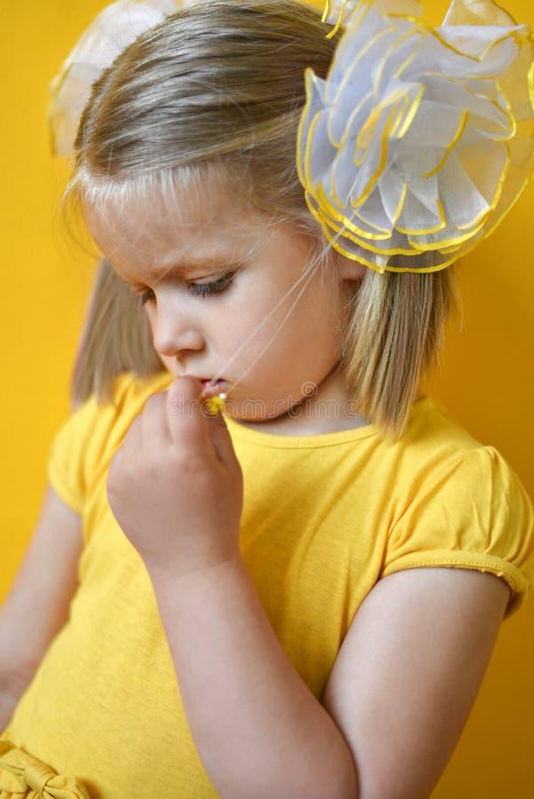 St?ende av den ledsna blyga lilla flickan i en gul kl?nning p? en gul bakgrund arkivbild