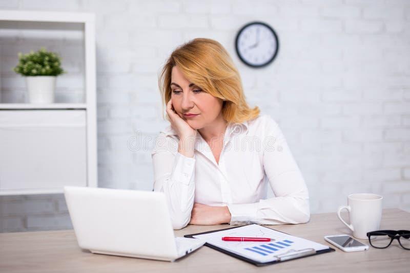 Stående av den ledsna eller trötta kvinnan för mogen affär i regeringsställning arkivbild