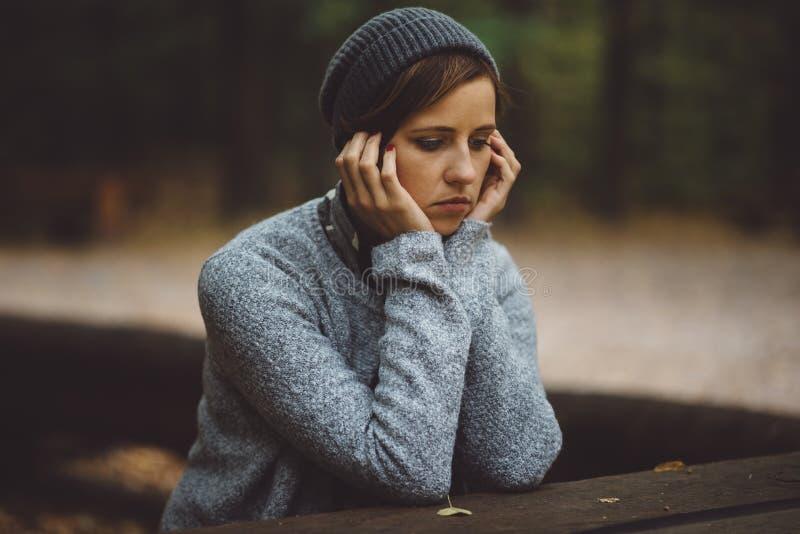 Stående av den ledsna kvinnan som bara sitter i skogensamhetbegreppet Millenial som handlar med problem och sinnesrörelser arkivbilder