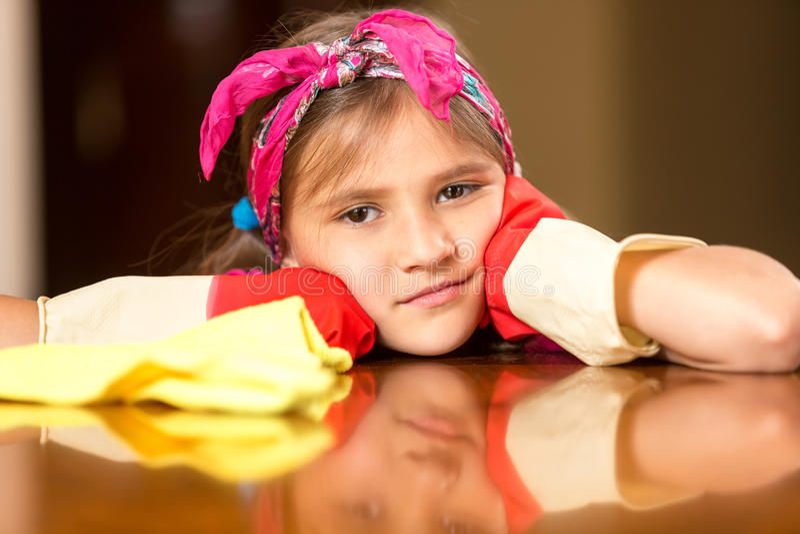 Stående av den ledsna lilla flickan i rubber handskar som gör ren träfliken arkivbild