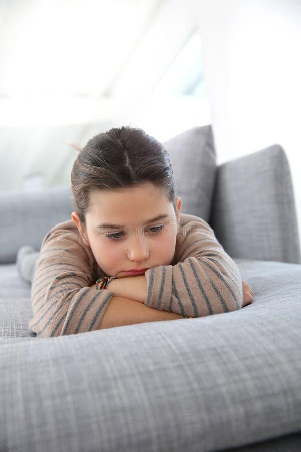 Stående av den ledsna lilla flickan som ligger på soffan arkivbild
