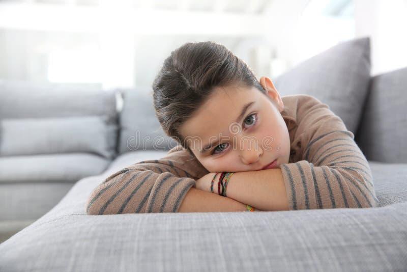 Stående av den ledsna lilla flickan som ligger på soffan arkivfoto