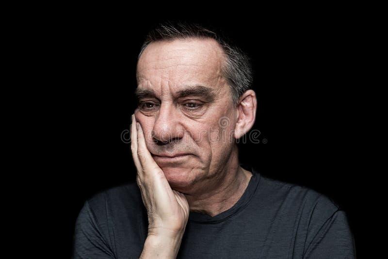 Stående av den ledsna olyckliga mannen på svart bakgrund royaltyfria bilder