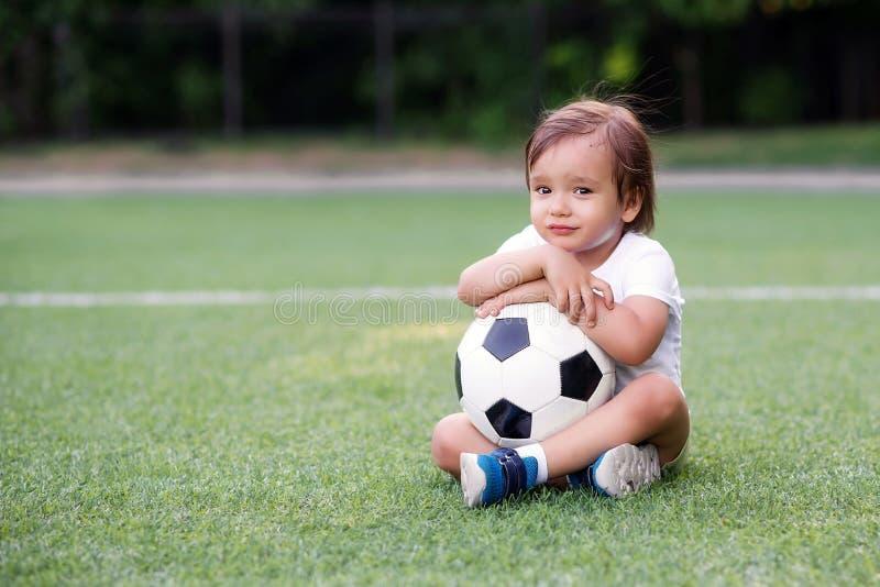 Stående av den ledsna olyckliga pojken som sitter på fotbollfält och rymmer med båda händer eller omfamnar fotbollbollen Maj är h royaltyfria foton