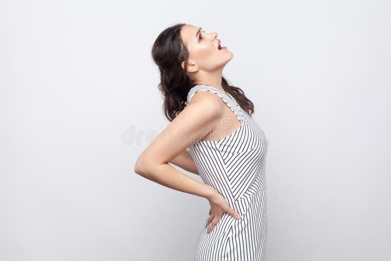 Stående av den ledsna sjuka unga brunettkvinnan med makeup och det randiga klänninganseendet som rymmer hennes rygg och skriker,  fotografering för bildbyråer