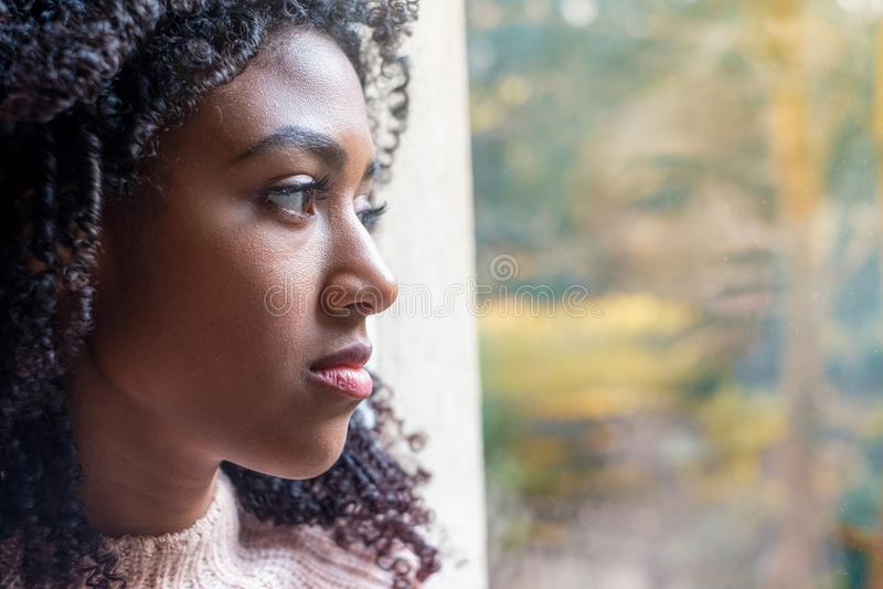 Stående av den ledsna svarta tonåringen bara hemma arkivfoton
