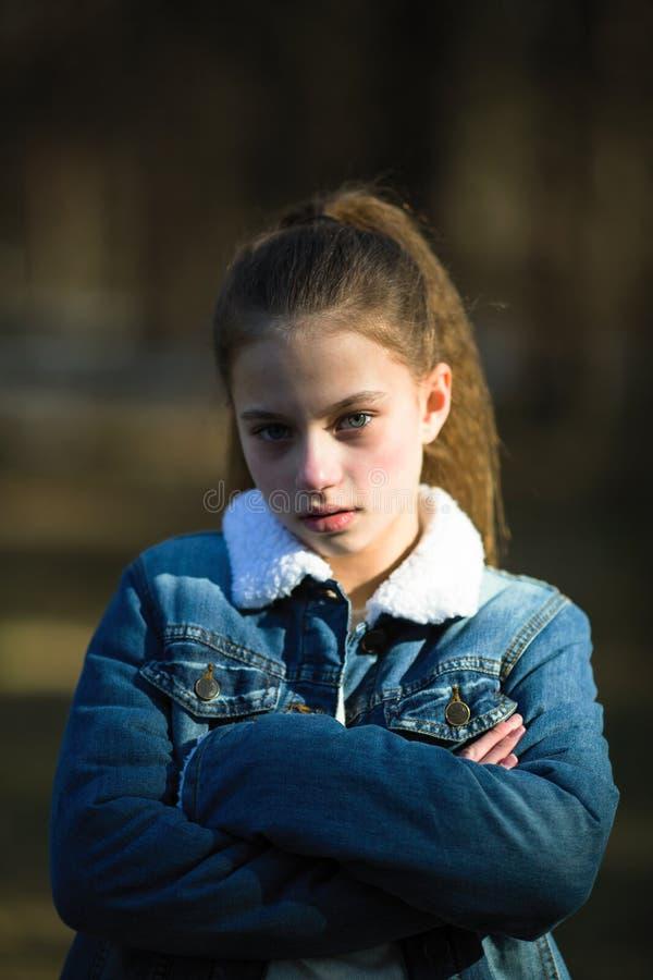 Stående av den ledsna unga flickan med långt hår utomhus royaltyfria foton