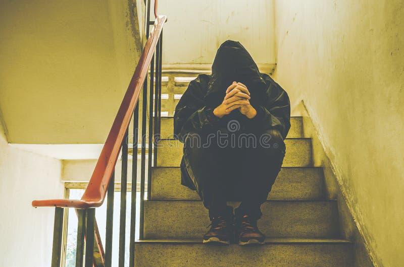 Stående av den ledsna unga mannen som täcker hans framsida med händer som sitter på gammal trappa royaltyfri bild