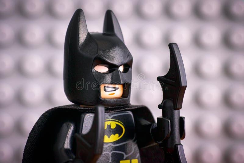 Stående av den Lego Batman minifiguren mot grå baseplate royaltyfri bild