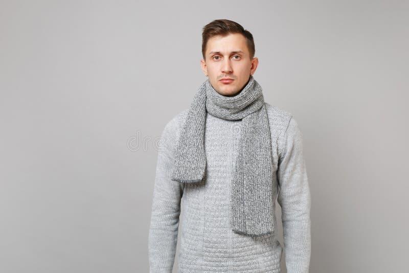 Stående av den likgiltiga unga mannen i den gråa tröjan, halsdukanseende som isoleras på grå väggbakgrund i studio Sunt royaltyfri fotografi