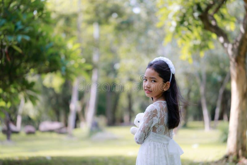 Stående av den lilla asiatiska flickan som ler i naturskogen med den bearbetade mjuka signalen royaltyfri fotografi