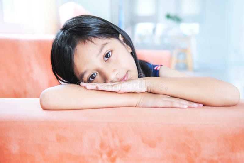 Stående av den lilla asiatiska flickan som ligger på soffan royaltyfri bild