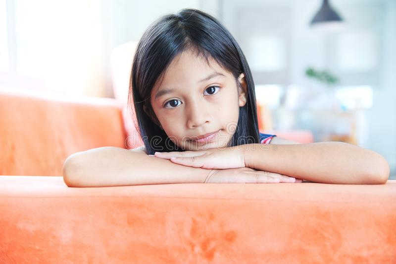 Stående av den lilla asiatiska flickan som ligger på soffan arkivbild