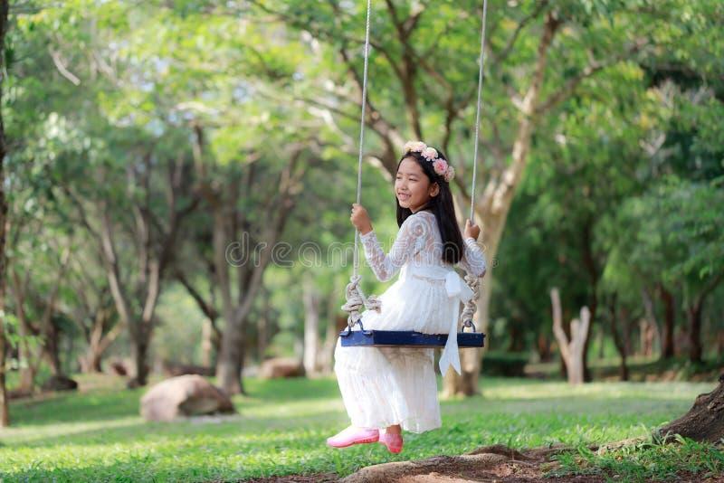 Stående av den lilla asiatiska flickan som spelar gungan under det stora trädet i djupet för vald fokus för naturskog det grunda  royaltyfri bild