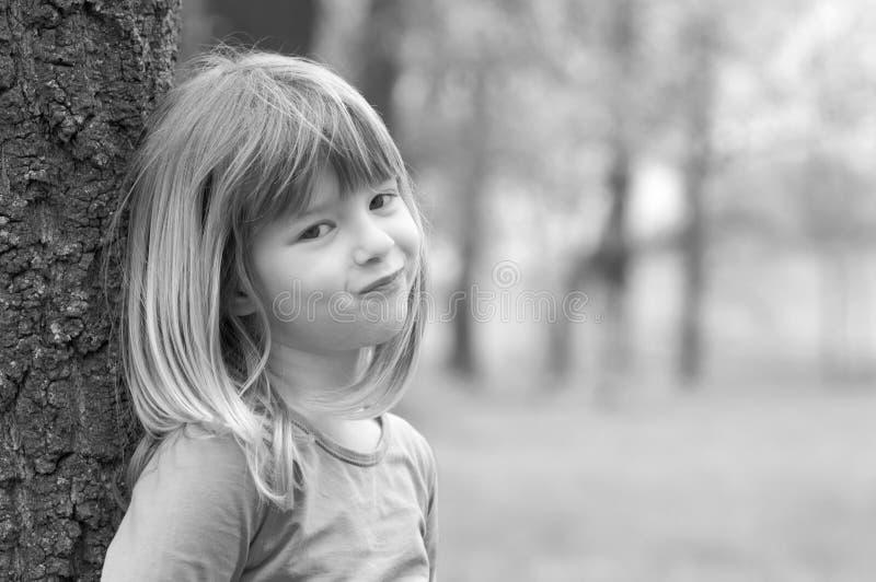 Stående av den lilla blonda flickan i vårskog arkivfoton