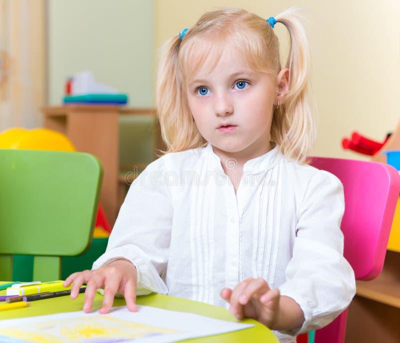 Stående av den lilla blonda flickan med blåa ögon arkivbild