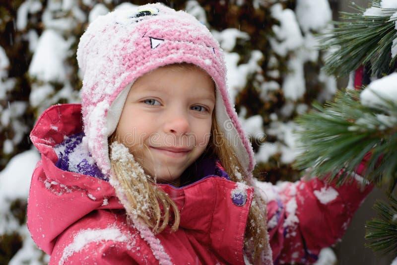 Stående av den lilla Caucasian blonda flickan på gran-träd bakgrund royaltyfri bild