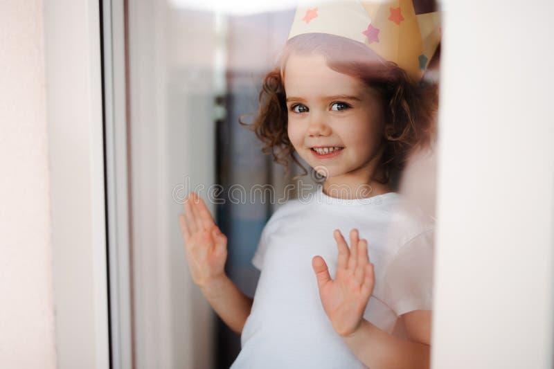 Stående av den lilla flickan med kronan hemma som ser ut ur ett fönster Skjutit till och med exponeringsglas royaltyfri bild