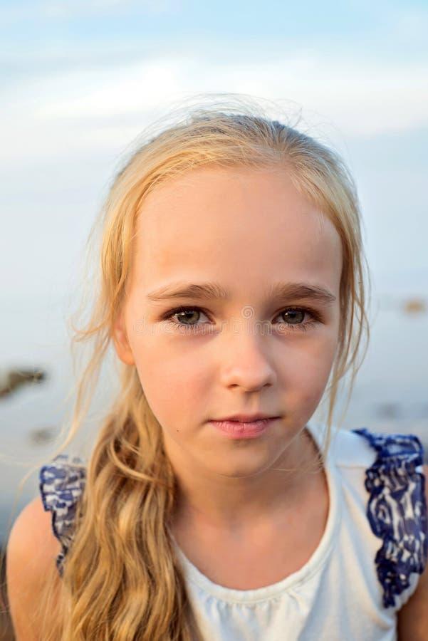 Stående av den lilla gulliga flickan på solnedgång royaltyfri bild