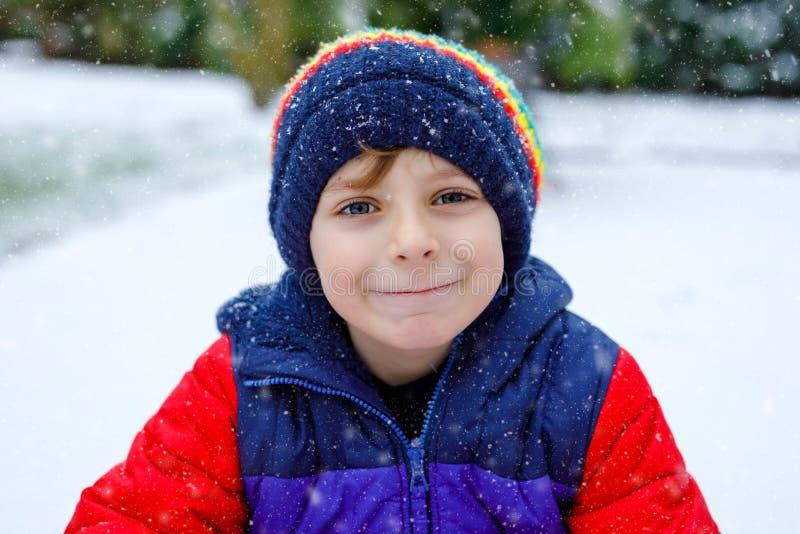 Stående av den lilla skolaungepojken i färgrik kläder som utomhus spelar under snöfall Aktiv fritid med barn in arkivfoton