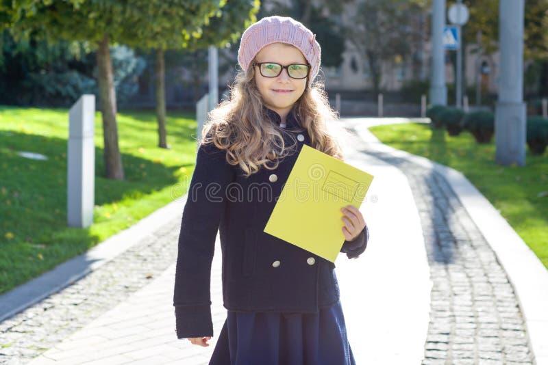 Stående av den lilla skolflickan med anteckningsböcker, bakgrundsväg till skolan arkivfoton