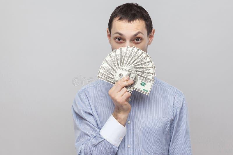 Stående av den listiga unga affärsmannen i den blåa skjortan som står, keeking och visar fanen av pengar och ser kameran arkivbilder