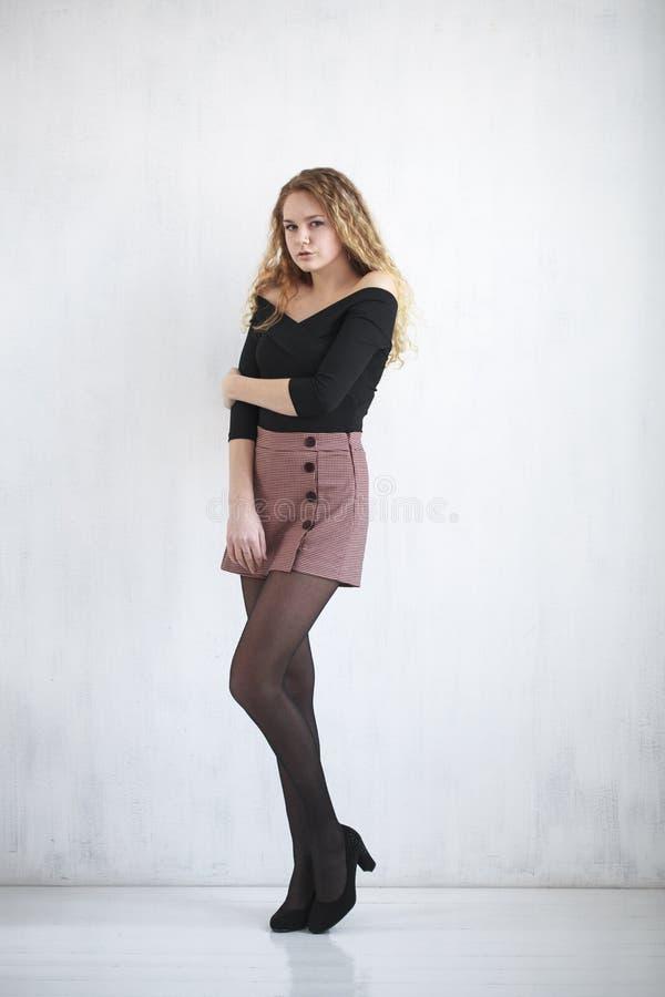 Stående av den lockiga blondinen för full längd i en svart blus och en kort kjol arkivbild