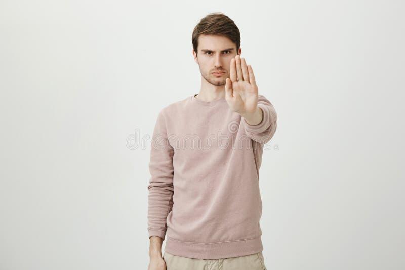 Stående av den lugna allvarliga unga mannen med borstet som sträcker handen in mot kamera med stopp- eller hållgest som står royaltyfri bild