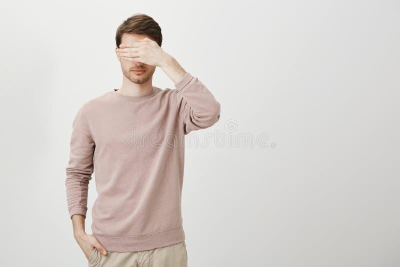 Stående av den lugna caucasian mannen med borstinnehavhanden i fack, medan täcka ögon och anseende mot grå färger royaltyfria bilder