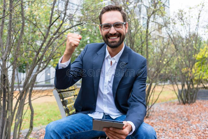 Stående av den lyckade affärsmannen som rymmer den digitala minnestavlan royaltyfri bild