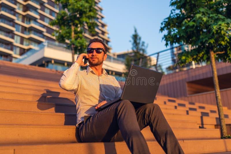 Stående av den lyckade affärspersonen med bärbara datorn och smartphonen som sitter på trappa mot modern skyskrapa i bakgrunden royaltyfri fotografi